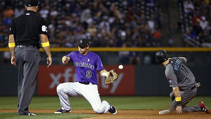 Colorado Rockies second baseman DJ LeMahieu misses the throw from home, allowing Arizona Diamondbacks' A.J. Pollock (11) the stolen base plus advance to third on the throwing error during the seventh inning of a baseball game Friday, Sept. 1, in Denver.