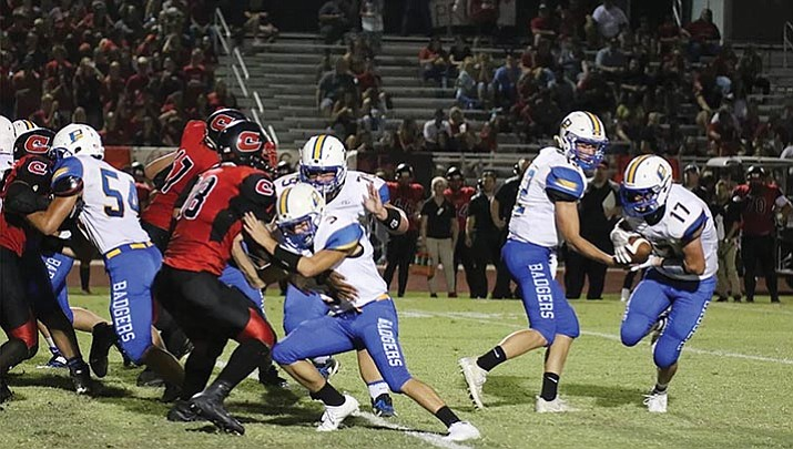 Prescott quarterback Austin Clark (12) hands off to tailback Ryan Greene (17) as the Badgers take on Combs on Friday, Sept. 1, in San Tan Valley. The Badgers won 49-6.