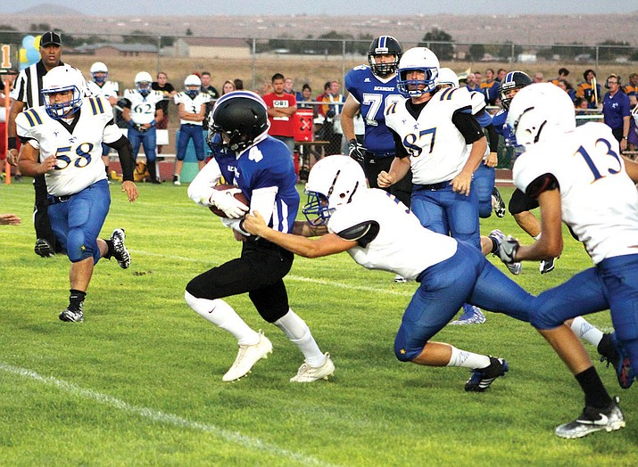 Kingman Academy's Nate Carter breaks through Kingman tacklers for a 14-yard gain Friday night.