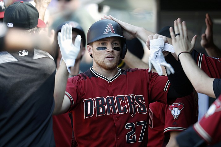 Arizona's Brandon Drury is congratulated as he returns to the dugout after hitting a two-run home run off Colorado Rockies starting pitcher German Marquez in the sixth inning of a baseball game Sunday, Sept. 3, in Denver. (David Zalubowski/AP)
