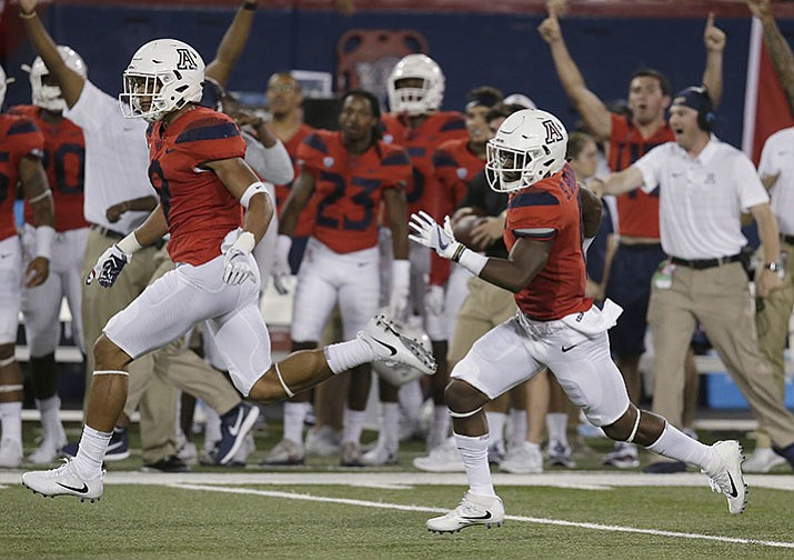 Arizona wide receiver Shun Brown, right, returns a punt for a touchdown against the Northern Arizona Lumberjacks during the first half of an NCAA college football game, Saturday, Sept. 2, in Tucson.