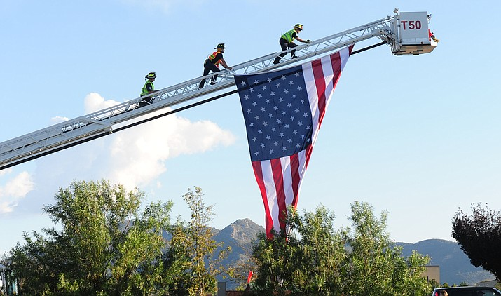 Central Yavapai firefighters hang a flag from the ladder truck during the Prescott Valley 9/11 Patriot Day Ceremony in 2015 at the Prescott Valley Civic Center.