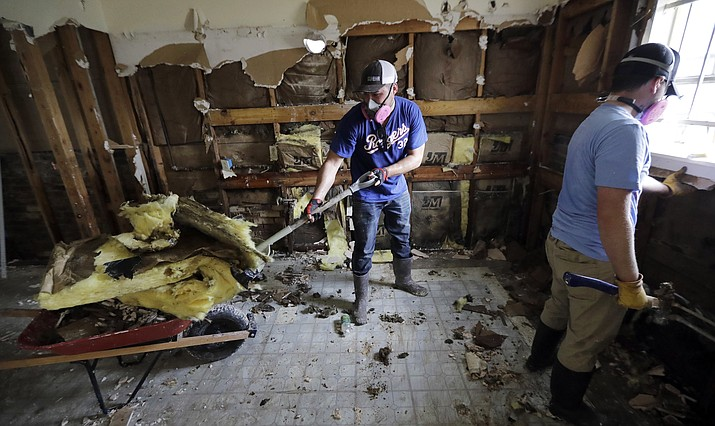 Volunteers Brock Warnick, right, and Colten Roberts remove drywall and insulation Monday, Sept. 4, 2017, from the Houston home of Julia Lluvia, which was damaged by floodwaters in the aftermath of Hurricane Harvey. (David J. Phillip/AP)