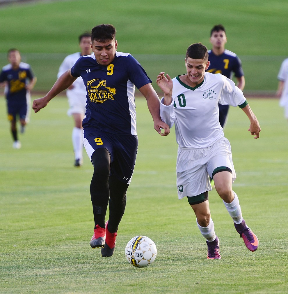 Yavapai's Carlo Quesada battles for the ball with Noe Ancira as the Roughriders take on the Phoenix College Bears Tuesday night at Mountain Valley Park in Prescott Valley. (Les Stukenberg/Courier).