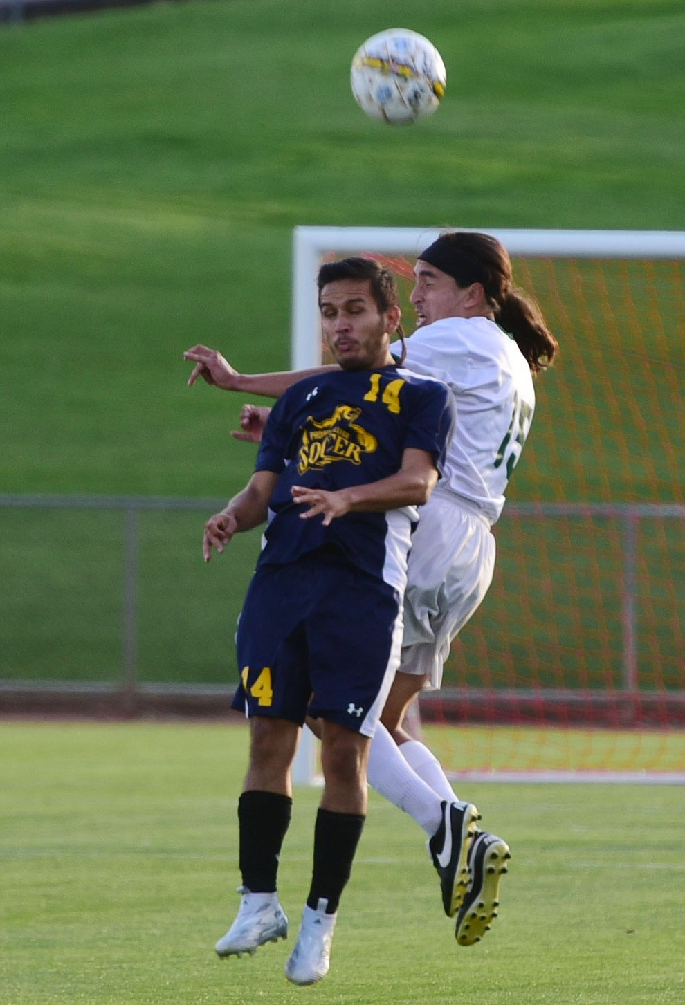 Yavapai's John Kanner heads the ball over Sebastian Aguas as the Roughriders take on the Phoenix College Bears Tuesday night at Mountain Valley Park in Prescott Valley. (Les Stukenberg/Courier).