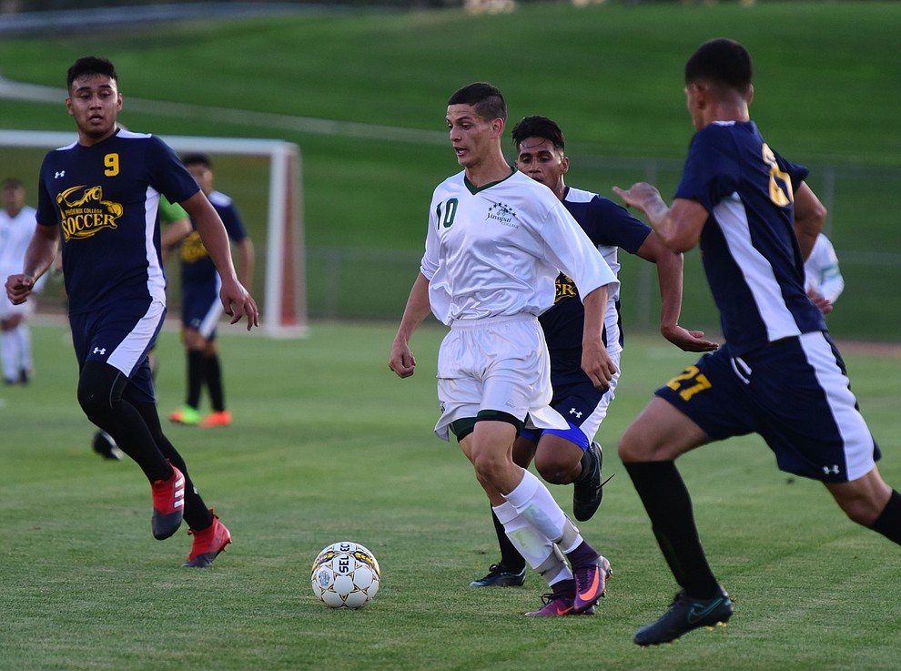Yavapai's Carlo Quesada moves the ball through a trio of defenders as the Roughriders take on the Phoenix College Bears Tuesday night at Mountain Valley Park in Prescott Valley. (Les Stukenberg/Courier).