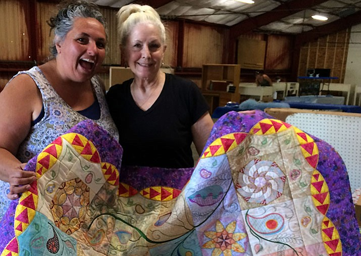 Homemaking/Craftsmanship Department's Trudy Annis (left)helps quilter Donna Domino enter her embroidered quilt Sept. 5. The fair runs Thursday through Sunday. (Sue Tone/Courier)