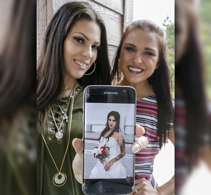 Arianna Pro, left, displays a photo of her in the wedding dress of Dawnetta Heinz, right, in Omaha, Neb., Wednesday, Sept. 6, 2017. Heinz has offered to share her wedding dress with brides on tight budgets. Two other women, including Arianna Pro have already worn the dress in the past month, and there's interest from several others. (AP Photo/Nati Harnik)