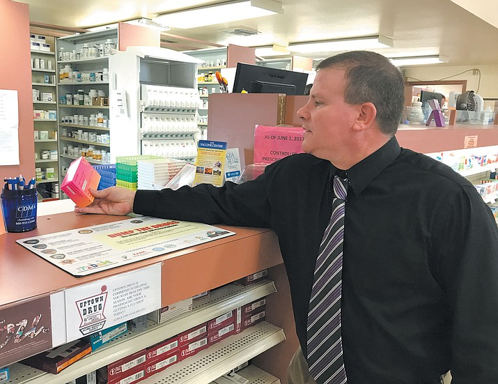 Uptown Drug owner and registered pharmacist Chris Proffit takes a look at one of the many versions of birth control pills available at his three stores.