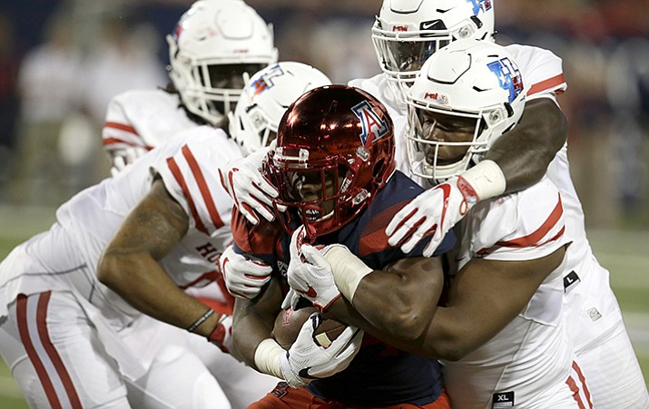 Houston defensive tackle Ed Oliver and his teammates tackle Arizona running back Zach Green during the first half of an NCAA college football game, Saturday, Sept. 9, in Tucson.