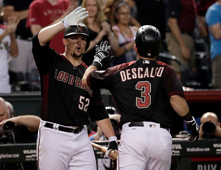 Arizona Diamondbacks' Daniel Descalso (3) high fives teammate Zack Godley (52) after hitting a solo home run against the San Diego Padres during the fifth inning Saturday, Sept. 9, in Phoenix. (Matt York/AP)