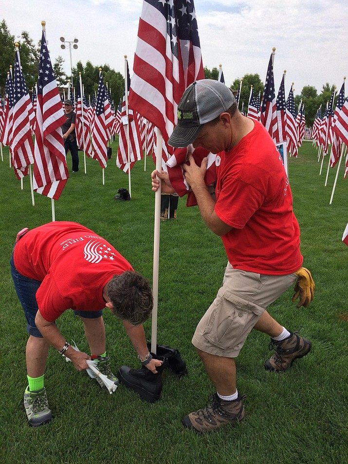 Darlene Packard, Healing Field event coordinator, left, and Ryan Judy, assistant town manager for Prescott Valley, place a pair of police boots with the flag honoring Nathaniel Webb, 56, who died in the World Trade Center attack Sept. 11, 2001. The Healing Field at the PV Civic Center, with 3,019 flags, remains in place through Sept. 15. (Sue Tone/Courier)