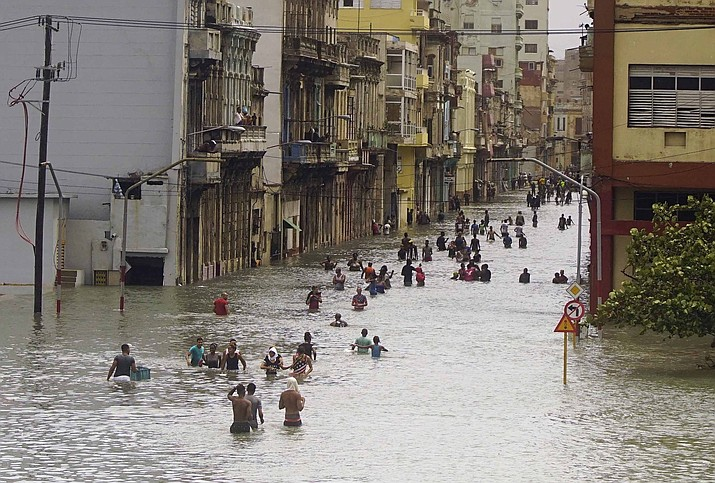 People move through flooded streets in Havana after the passage of Hurricane Irma, in Cuba, Sunday, Sept. 10, 2017. The powerful storm ripped roofs off houses, collapsed buildings and flooded hundreds of miles of coastline after cutting a trail of destruction across the Caribbean. Cuban officials warned residents to watch for even more flooding over the next few days. (Ramon Espinosa/AP)