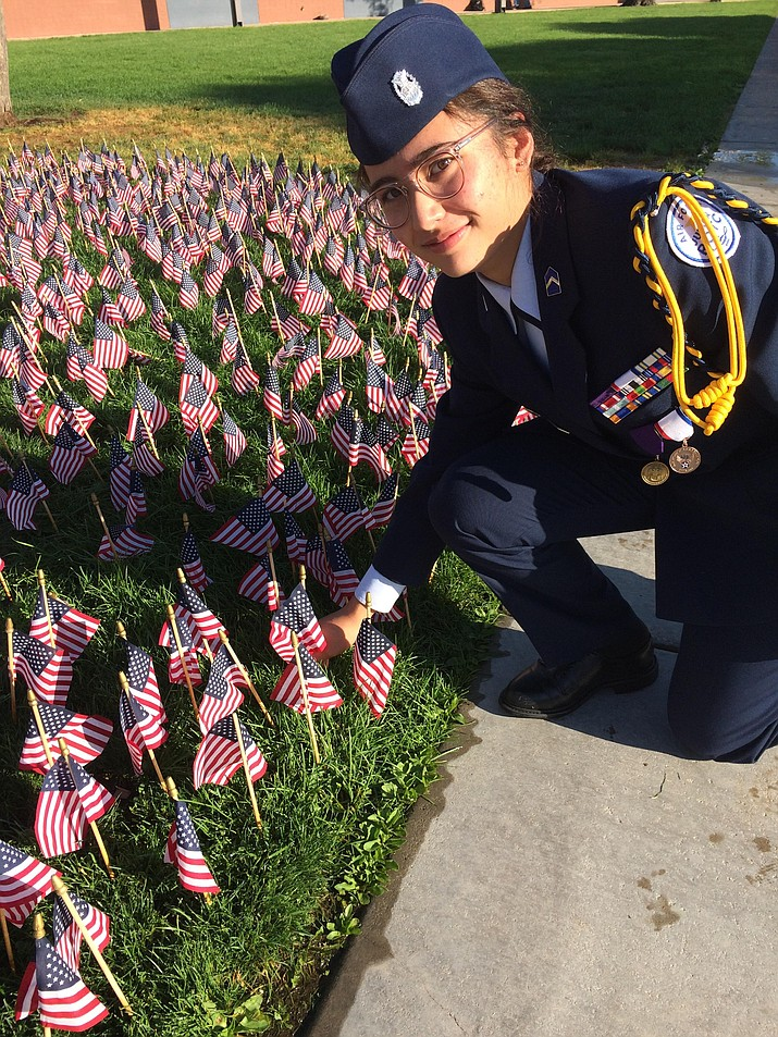 Prescott High School JROTC Cadet Major Alisha Pestana plants one of almost 3,000 miniature flags at the base of the school's center flagpole. (Nanci Hutson/Courier)