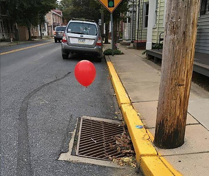 "The Lititz, Pennsylvania Police Department posted photos of red balloons a prankster tied to a pair of sewer grates. A red balloon is the calling card of Pennywise, the sewer-dwelling, child-eating clown in Stephen King's horror novel ""It."" The hotly anticipated movie version opened in theaters on Friday. (Lititz Police Department)"