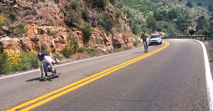 Two skateboarders head down the switchbacks on SR 89A from the top of Mingus Mountain toward Prescott on Labor Day Weekend. (VVN/Vyto Starinskas)