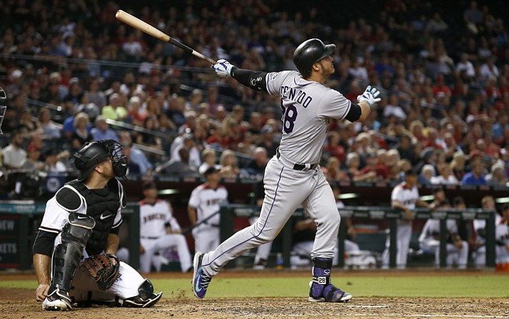 Colorado Rockies' Nolan Arenado, right, watches the flight of his three-run home run Monday, Sept. 11, 2017, in Phoenix. (Ross D. Franklin/AP)