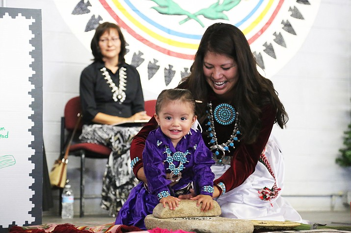 A mother and her daughter grind corn at the Navajo Nation Fair Baby Contest. Submitted photo