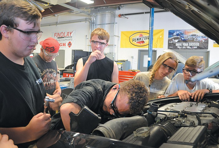 Junior Gage Elder, center, gets neck deep in radiator repairs while his Intro to Auto cohorts look on.