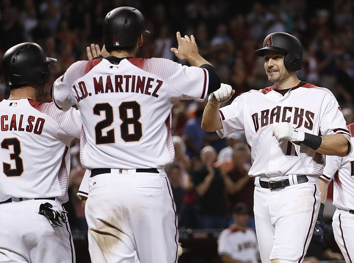 Arizona Diamondbacks' A.J. Pollock, right, high-fives J.D. Martinez (28) and Daniel Descalso (3) after hitting a three-run home run against the Colorado Rockies during the seventh inning of a baseball game, Wednesday, Sept. 13, in Phoenix. (Matt York/AP)