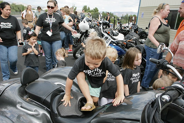 About 40 children at the Flip City Gym and Learn Preschool in Cottonwood receive a hands-on learning experience about motorcycle safety and motorcycle awareness when members of the Verde Valley chapter of the Modified Motorcycle Association of Arizona show off their two-wheelers. Thursday's event was a precursor of sorts for this weekend's Thunder Valley Rally, as the preschool will hold a Parents Night Out to allow parents to bring their children to the preschool before the enjoy the Rally's various festivities. For more information about Flip City's preschool program, call 928-639-2852. (Photo by Bill Helm)