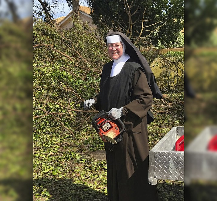Sister Margaret Ann holds a chain saw near Miami, Fla. where she was cutting trees to clear the roadways around Archbishop Coleman Carrol High School in the aftermath of Hurricane Irma. (Miami-Dade Police Department via AP)