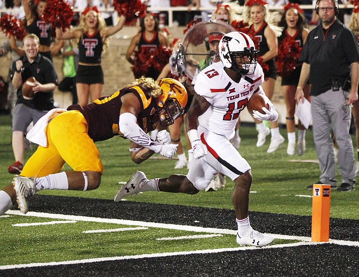Texas Tech's Cameron Batson scores a first-half touchdown while being chased by Arizona State's Dasmond Tautalatasi during the first half of an NCAA college football game Saturday, Sept. 16, in Lubbock, Texas. (Mark Rogers/Lubbock Avalanche-Journal via AP)