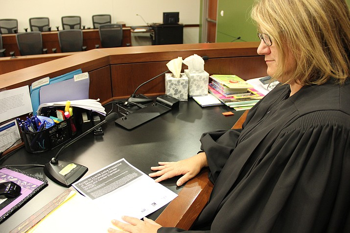 Yavapai County Superior Court Judge Anna Young examines a recently released bench card by the National Council of Juvenile and Family Court Judges. (Max Efrein/Courier)