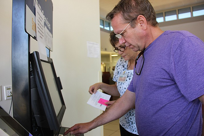 An Arizona Department of Transportation Motor Vehicle Division visitor in Prescott navigates the location's service kiosk with the help of an MVD employee.