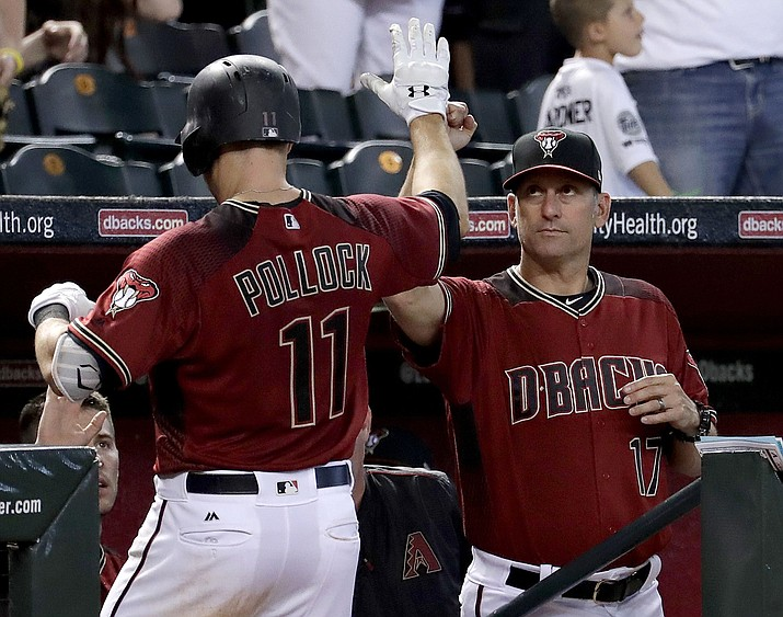 Arizona Diamond-backs' A.J. Pollock, left, greets manager Torey Lovullo (17) after hitting a solo home run against the Cincinnati Reds during a baseball game, Sunday, July 9, 2017, in Phoenix. (AP Photo/Matt York)