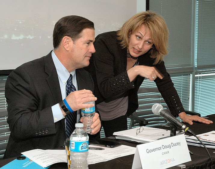 Gov. Doug Ducey chats Thursday with Sandra Watson, president of the Arizona Commerce Authority, ahead of the meeting of the board. (Capitol Media Services photo by Howard Fischer)