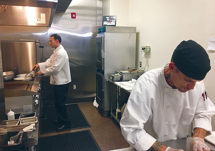 Kris Glass, foreground, and Luigi Garibaldi work on preparing a meal at Garibaldi's deli.