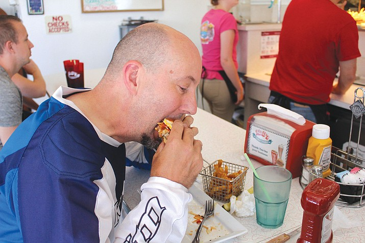 Mike Pangerl of Princeton, Minnesota, enjoys a burger Friday at Mr. D'z Route 66 Diner. He said he'd never heard of National Cheeseburger Day, which is Sept. 18, but he eats a couple of them every month.