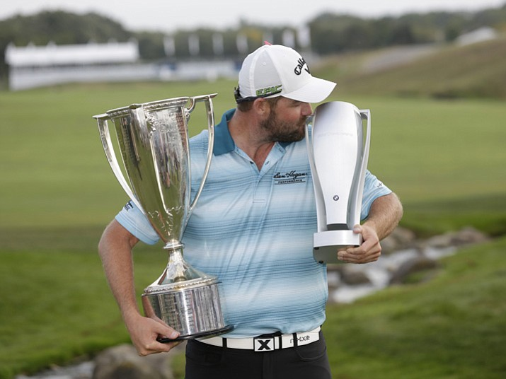 Marc Leishman smiles as he poses with the Wadley Cup, left, and kisses the BMW Championship trophy after winning the BMW Championship golf tournament at Conway Farms Golf Club, Sunday, Sept. 17, 2017, in Lake Forest, Ill. (Charles Rex Arbogast/AP)