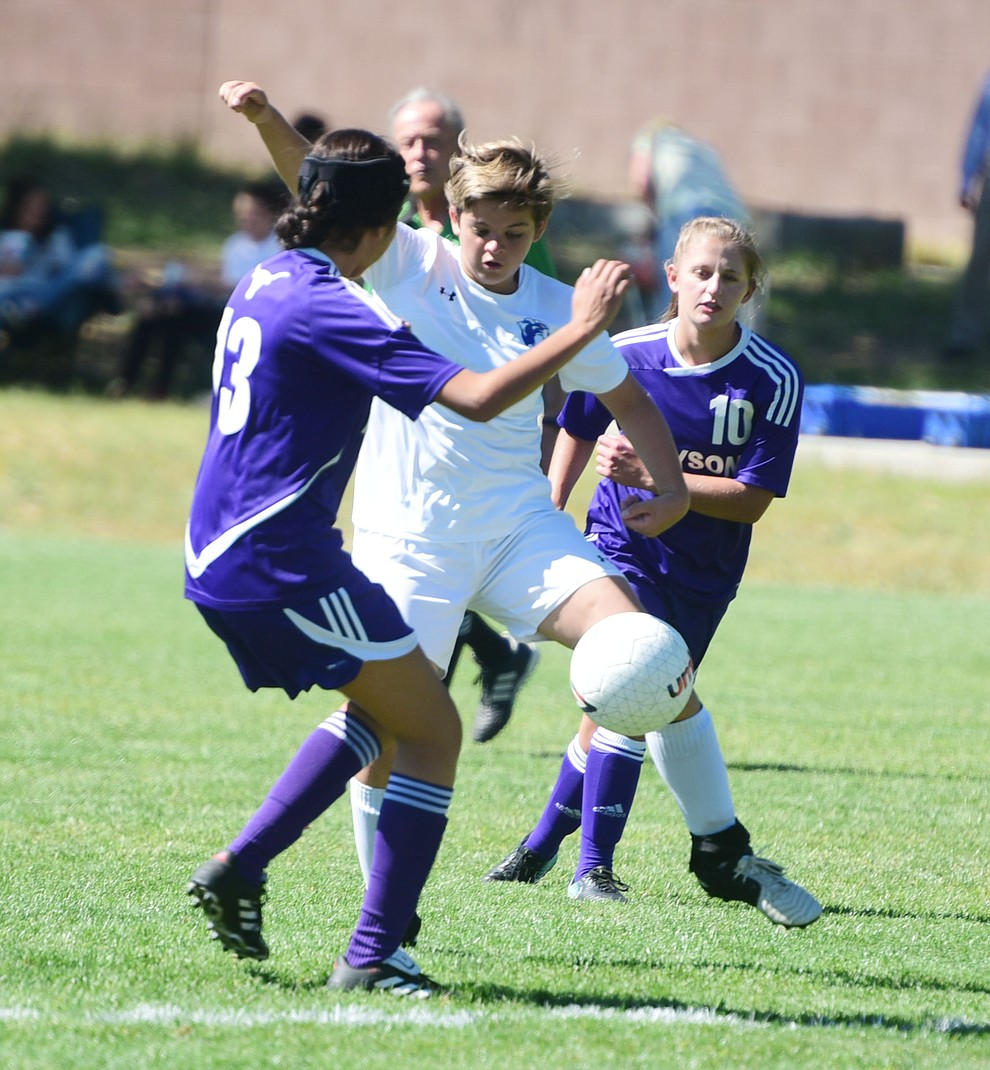 Chino Valley's Coury Hawks passes the ball between a pair of defenders as the Cougars routed Payson in a girls soccer matchup Tuesday afternoon in Chino Valley. (Les Stukenberg/Courier)