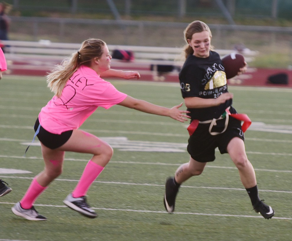 Senior Mica Nellis evades the tackle of junior Grace Kelley as the seniors played the juniors in Bradshaw Mountain's annual Powderpuff football game Wednesday in Prescott Valley. The juniors won a close fought game 12-6 despite the seniors last minute heroic comeback attempt. (Les Stukenberg/Courier).
