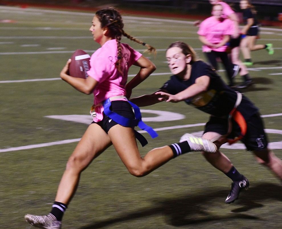 Junior Ryleigh Romney turns the corner on senior Mica Nellis as the seniors played the juniors in Bradshaw Mountain's annual Powderpuff football game Wednesday in Prescott Valley. The juniors won a close fought game 12-6 despite the seniors last minute heroic comeback attempt. (Les Stukenberg/Courier).