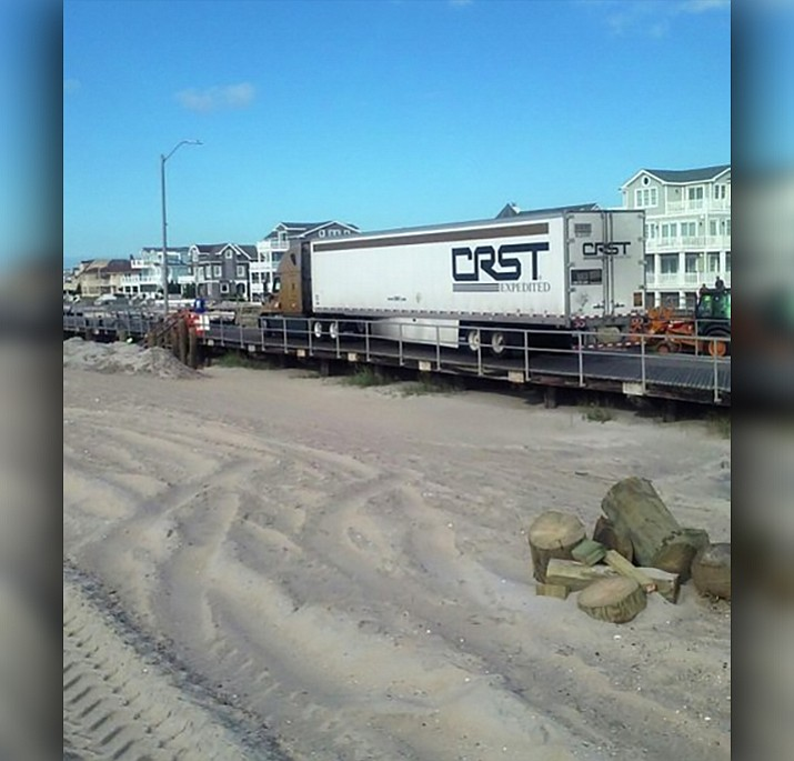 In this Wednesday, Sept. 20, 2017 photo, a tractor trailer is shown stuck on the boardwalk in Ventnor, N.J. Police said that the tractor trailer first drove onto the boardwalk at Albany Avenue in Atlantic City early Wednesday. It then drove about 2 miles (3.2 kilometers) south, close to the end of the boardwalk in Ventnor. (Fred Maccarella via AP)