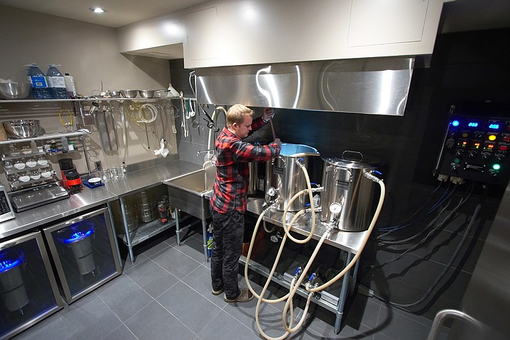 "In this 2013 photo provided by Kal Wallner, Wallner stirs the grain in his home brewery room in Ottawa, Canada. Wallner is an electrical engineer who designed a brewing system for himself that he now sells online at TheElectricBrewery.com. With an electric system, ""you can brew indoors in your flip-flops,"" says Wallner. (Kal Wallner/TheElectricBewery.com via AP)"