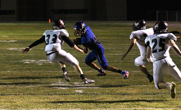 Camp Verde senior Kevin Oothoudt tries to evade Tonopah Valley tacklers during the Cowboys' 36-0 loss to the Phoenix on Friday night. (VVN/James Kelley)