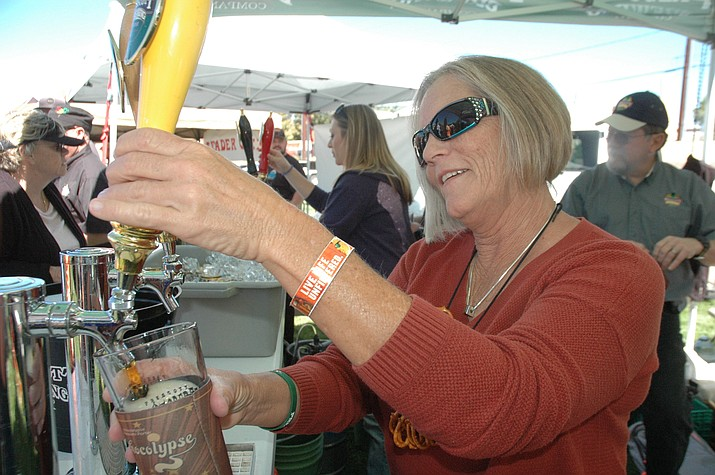 Susan Brown pours a glass of Prescott Brewing Company's Oktoberfest while wearing a pretzel necklace at Prescott Oktoberfest on Saturday, Sept. 23, at Mile High Middle School. (Jason Wheeler/Courier)