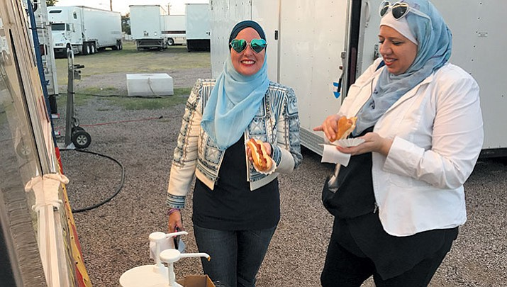 Deedra Abboud, left, and Tara Ijai enjoy a beef hot dog at the fair.