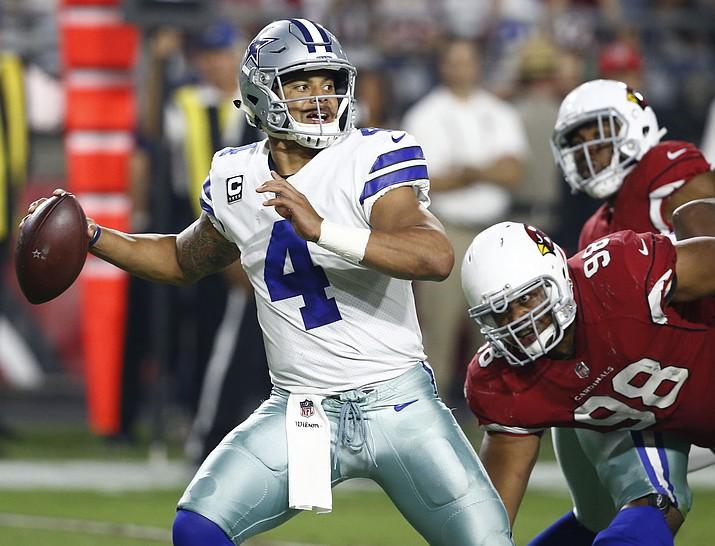 Dallas Cowboys quarterback Dak Prescott (4) throws as Arizona Cardinals nose tackle Corey Peters (98) pursues during the second half Monday, Sept. 25, 2017, in Glendale. The Cowboys beat Arizona on Monday Night Football, 28-17. (Ross D. Franklin/AP)