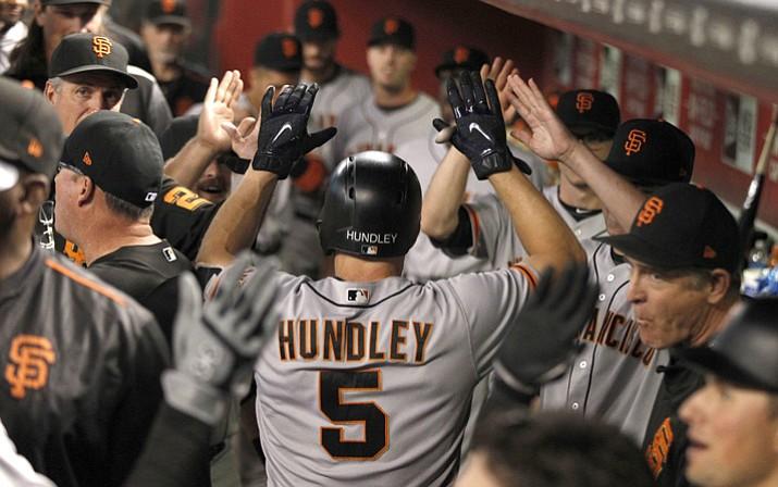 San Francisco Giants' Nick Hundley gets high-five from teammates after hitting a three-run home run against the Arizona Diamondbacks in the fourth inning inning Monday, Sept. 25, 2017 in Phoenix. (Darryl Webb/AP)
