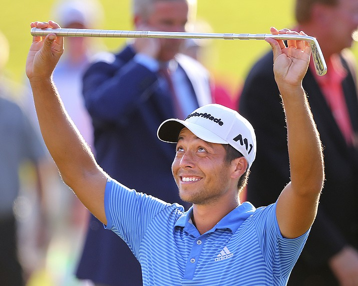 Xander Schauffele holds up the Calamity Jane trophy after winning the Tour Championship golf tournament at East Lake Golf Club in Atlanta, Sunday, Sept. 24, 2017, in Atlanta. (Curtis Compton/Atlanta Journal-Constitution via AP)