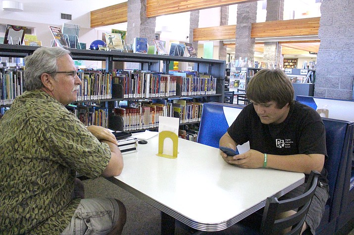 Noah Esquibel checks his phone at the Kingman library during a visit with MIKID respite provider John Christner. They use the library for social purposes and its WiFi access.
