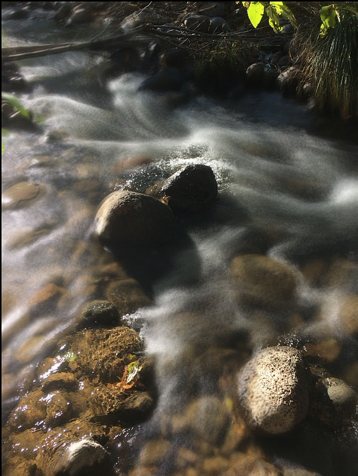 The rushing water of Clear Creek around stationary rocks.