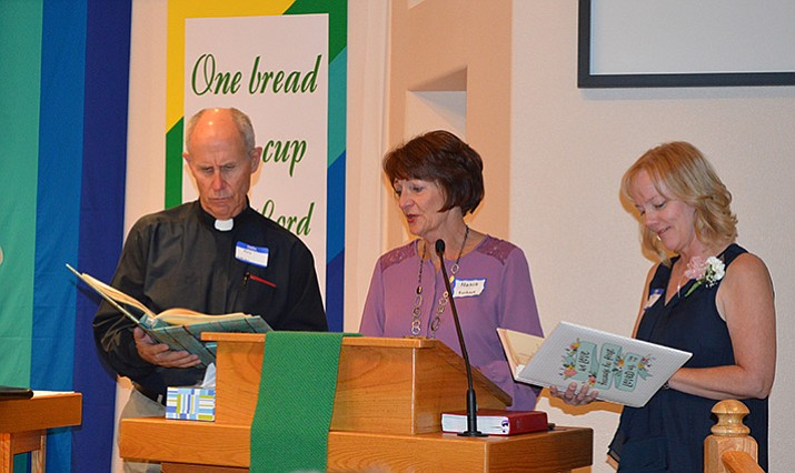 Rev. Kirk Anderson and Brita Hammit, right, receive memory books filled with letters, drawings and remembrances from the congregation from event co-chair Nance Busboom. (Courtesy photo)
