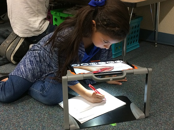 Cindy Castellone chooses to use her magnifying device on the fifth-grade classroom floor to illuminate and enlarge long division problems in her math class.