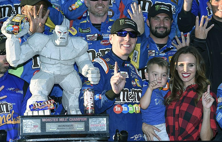Kyle Busch, third from right, poses with the trophy with his son Brexton, second from right, and wife Samantha, right, after he won the NASCAR Cup Series auto race, Sunday, Oct. 1, 2017, at Dover International Speedway in Dover, Del. (Nick Wass/AP)